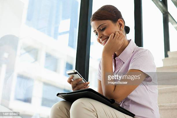 Jeune femme d'affaires assis sur les escaliers et en utilisant le téléphone intelligent