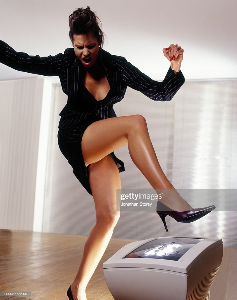 Young businesswoman stamping on computer screen with stilletto heel : Stock Photo