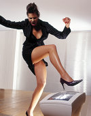 Young businesswoman stamping on computer screen with stilletto heel