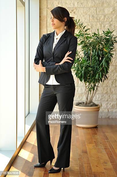 Junge Geschäftsfrau im Büro mit einem großen Fenster