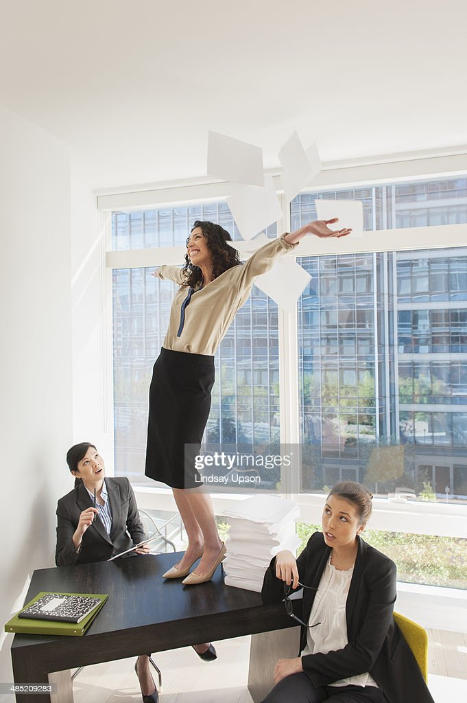 Young businesswoman standing on desk throwing papers mid air : Photo