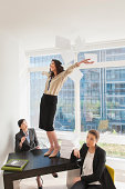 Young businesswoman standing on desk throwing papers mid air