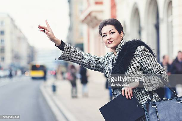 Young businesswoman stoping a taxi cab