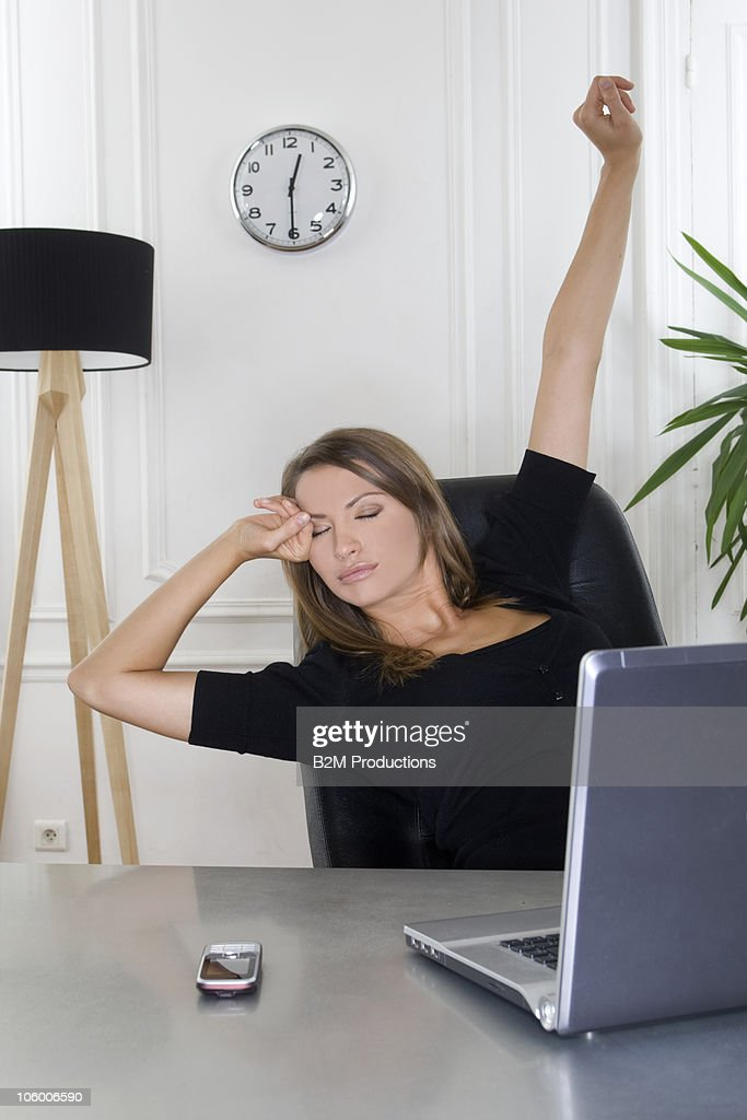 Young businesswoman stretching at desk : Stock Photo