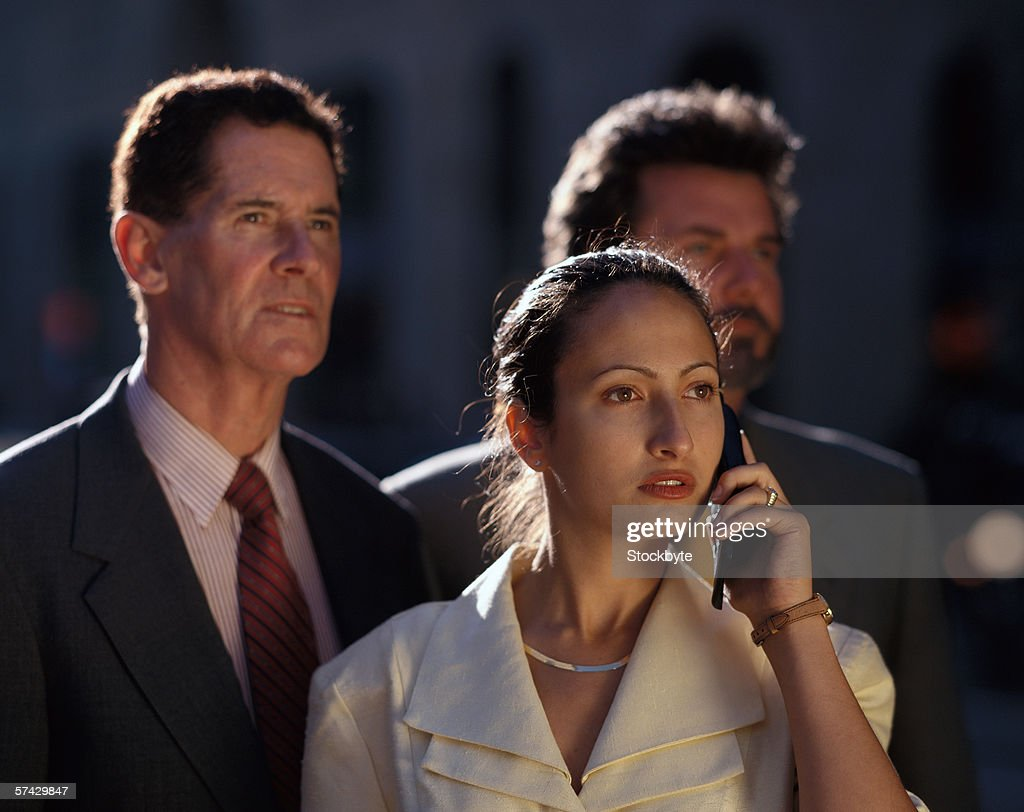 Young businesswoman talking on a mobile phone with two businessmen standing behind her : Stock Photo