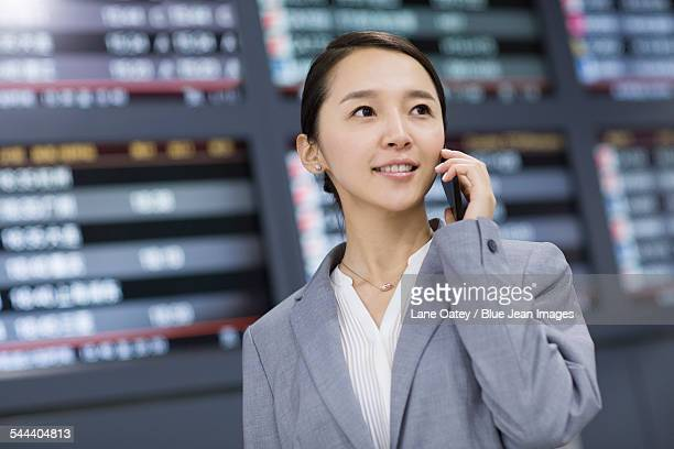 Young businesswoman talking on phone in airport