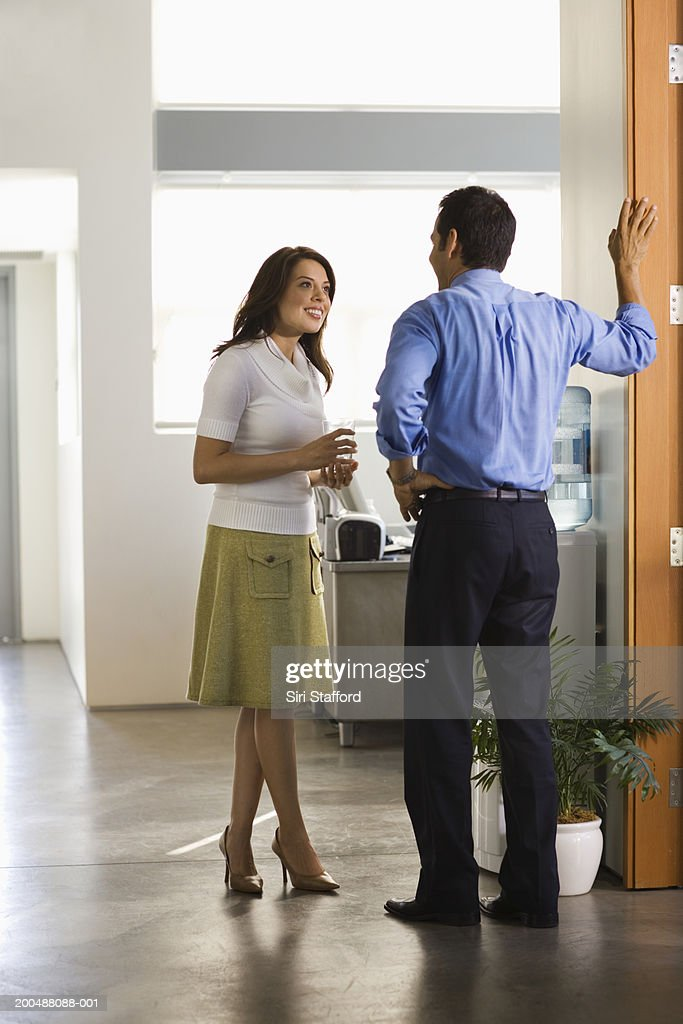 Young businesswoman talking to male colleague : Stock Photo