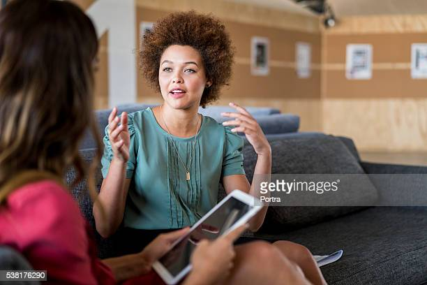 Young businesswoman talking with colleague on sofa