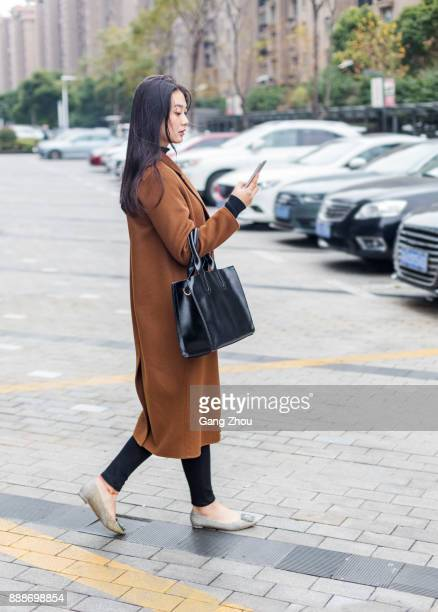young businesswoman texting messages on street