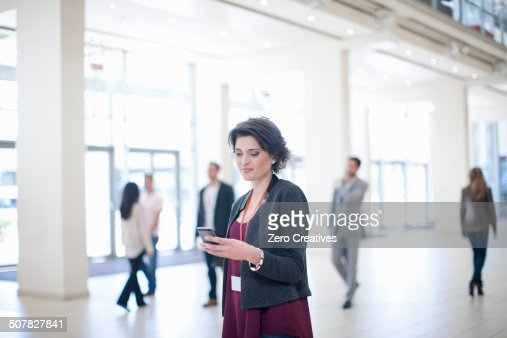 Young businesswoman texting on smartphone in conference centre corridor