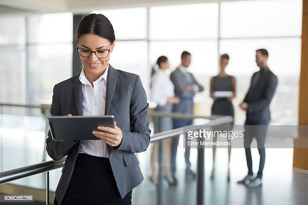 Young businesswoman using digital tablet in office building hallway.