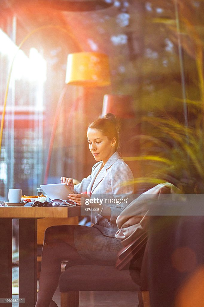 Young businesswoman using her digital tablet at restaurant