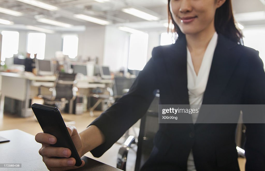 Young Businesswoman using her phone at the office : Stock Photo