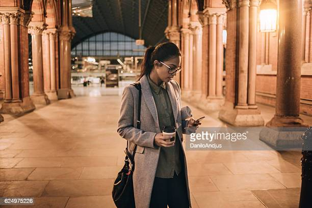 young businesswoman using her smartphone on the way after work