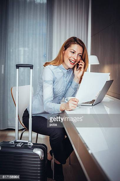 Young businesswoman using mobile phone  in  hotel room