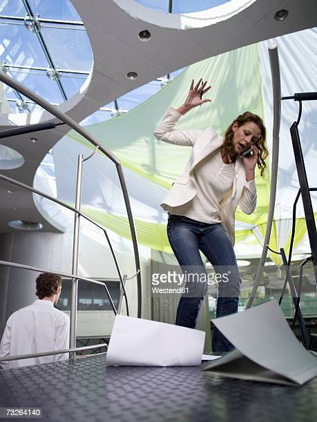 Businesswoman using mobile phone, papers falling on floor