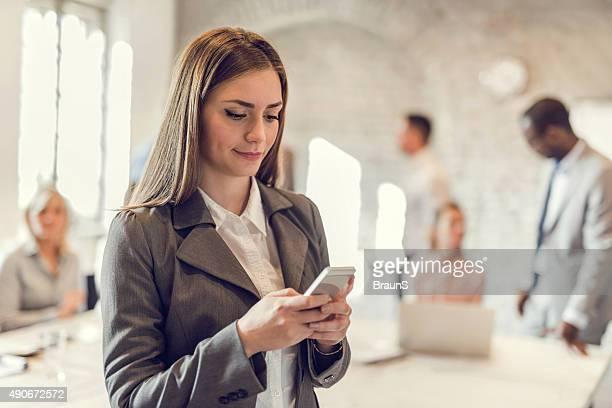 スマートフォンを使用して若いビジネスウーマンのオフィスにお問い合わせください。