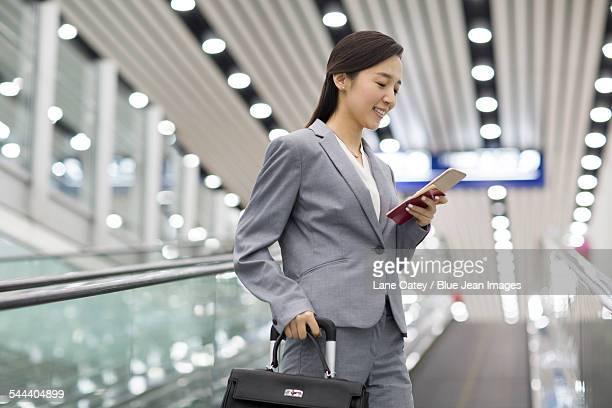 Young businesswoman using smart phone on escalator