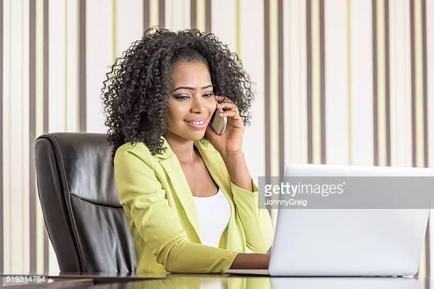 Jeune femme d'affaires à l'aide de son smartphone et l'ordinateur portable
