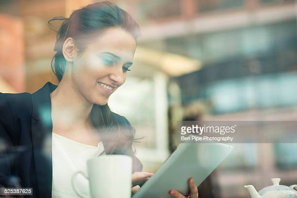 Young businesswoman using touchscreen on digital tablet in cafe, London, UK