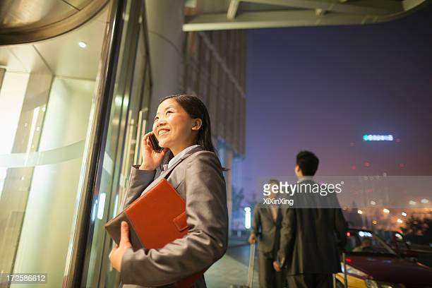 Young businesswoman walking and talking on her cell phone