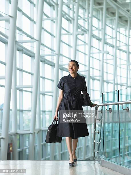 Young businesswoman walking up stairway in airport, smiling