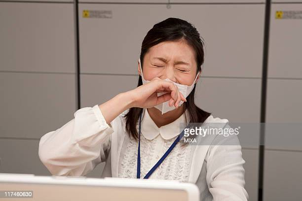 Young businesswoman wearing mask and sneezing