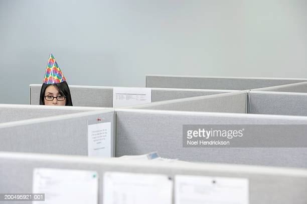 Young businesswoman wearing party hat in cubicle, high section