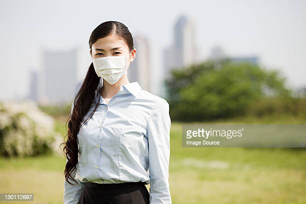 Young businesswoman wearing pollution mask