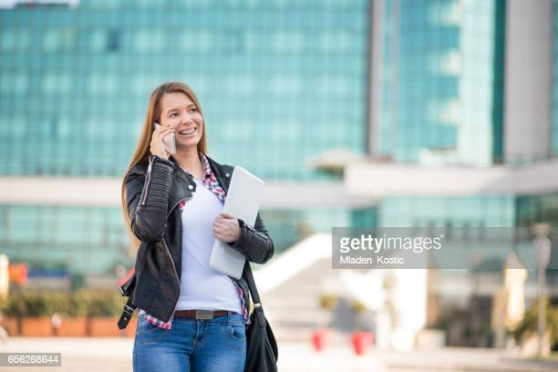 Young businesswoman web designer talking on phone outside office building