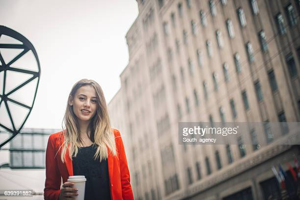 Young businesswoman with a coffee to go