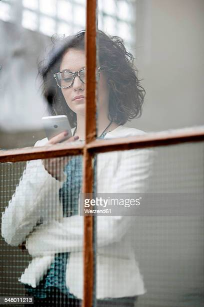 Young businesswoman with cell phone behind window
