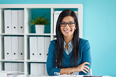 Young businesswoman with glasses working in modern office