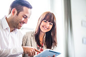 Portrait of young businesswoman with male colleague using digital tablet in office