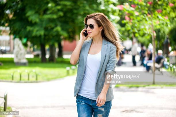 Young Businesswoman with Phone Walking at park