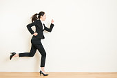 Young asian businesswoman with running on white background of indoor. business and management Way to success