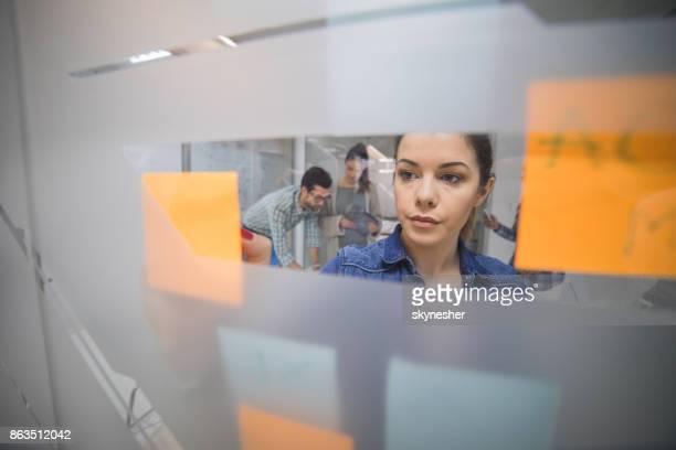 Junge Geschäftsfrau schreiben Businessplan auf selbstklebende Notizen im Büro.