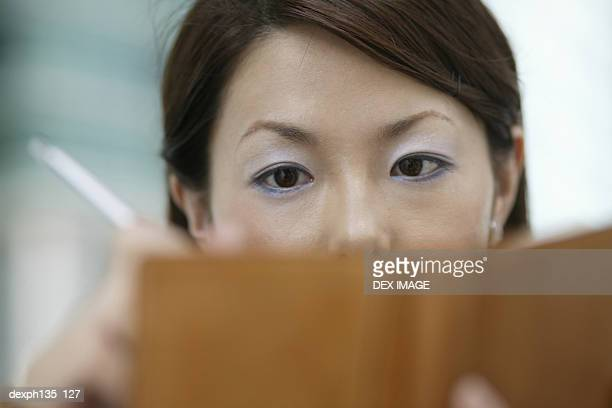 Young businesswoman writing into a diary