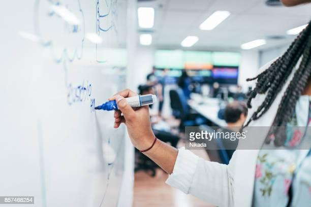 Junge Geschäftsfrau Schreiben von Notizen an Bord im Büro