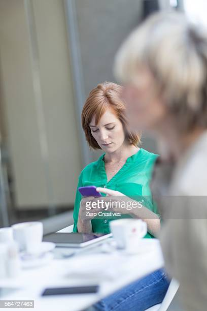 Young businesswomen reading smartphone texts on hotel terrace