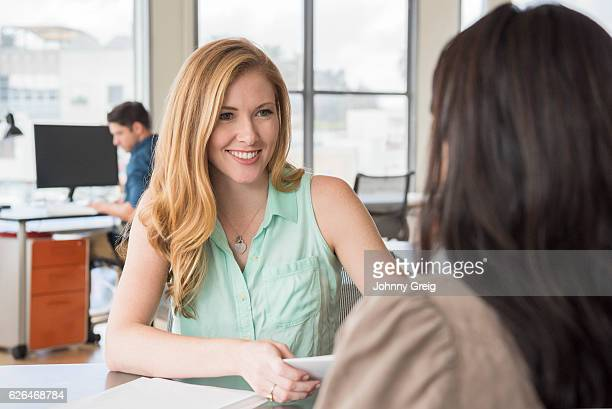Young businesswomen with long blonde hair smiling towards colleague