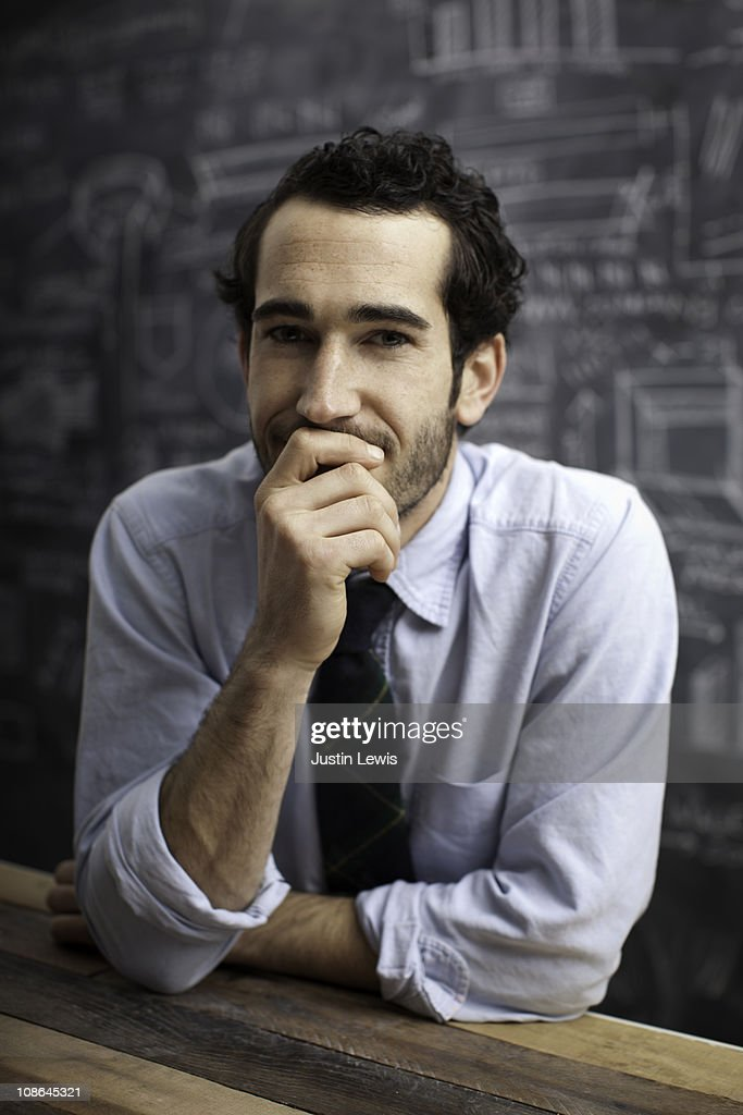 Young bussiness man smiling with chalkboard behind : Stock Photo