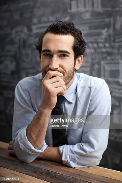Young bussiness man smiling with chalkboard behind