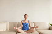 Young calm woman meditating in easy pose at home sitting on sofa, holding hands in chin mudra yogic gesture, practicing yoga in cozy living room, breathing air exercises, no stress, spiritual growth