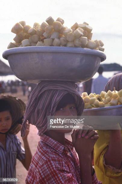 Young cambodian carrying sugar cane on his head in Angkor park October 1989