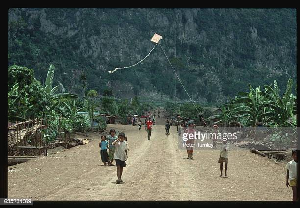 Young Cambodian refugees walk and one flies a kite in a street in Site 2 refugee camp