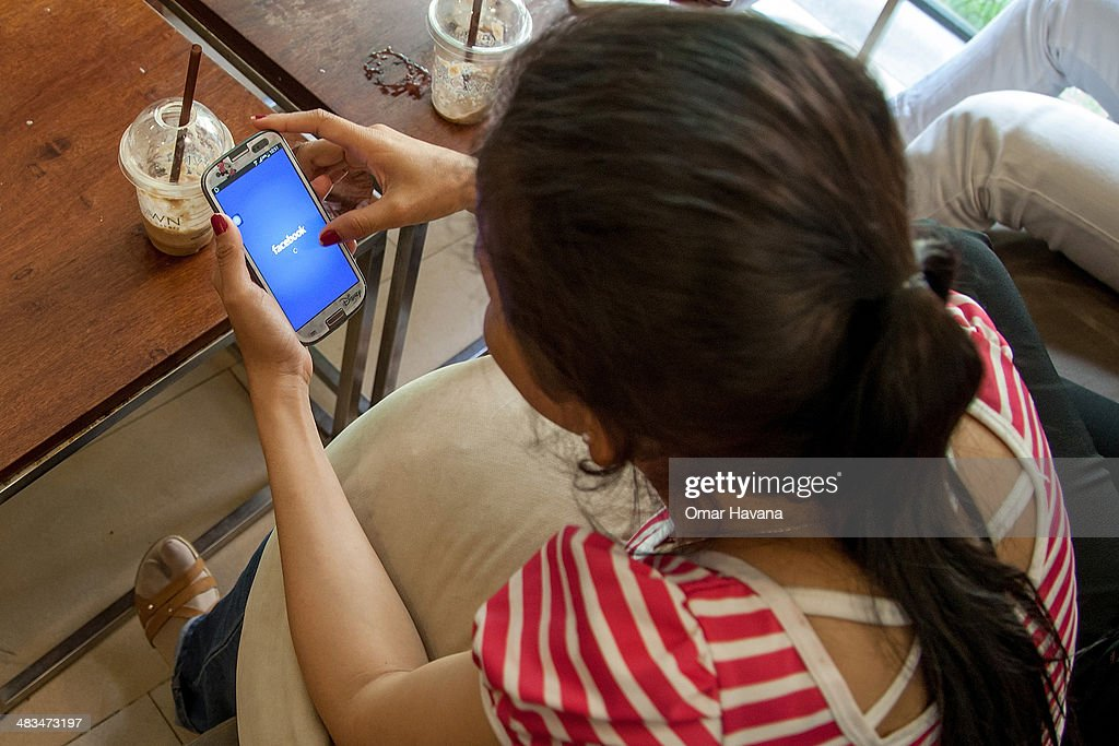 A young Cambodian uses her smartphone to check a social network in a local restaurant on April 9 2014 in Phnom Penh Cambodia Leaked to the media for...