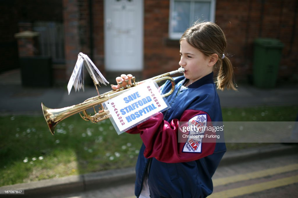 A young campaigner plays a trumpet as she holds a sign as protesters demonstrate to keep major health services at the scandal hit Stafford Hospital on April 20, 2013 in Stafford, England. The march was organised by the Support Stafford Hospital campaign group who are fighting cuts to major health services at the hospital. The Health regulator monitor has appointed two special administrators to produce a plan for the reorganisation of future services.