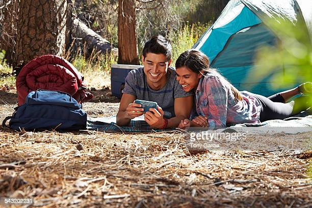 Young camping couple looking at smartphone in forest, Los Angeles, California, USA