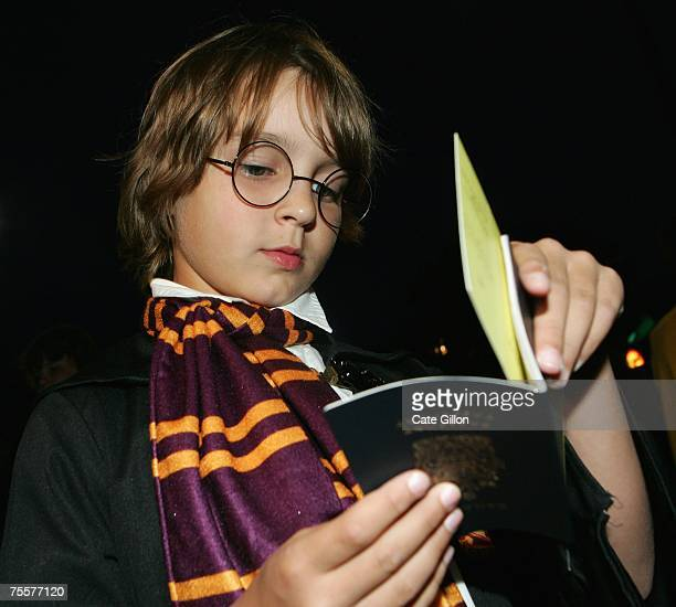 A young Canadian fan dressed up as Harry Potter takes his ticket from within his passport before meeting author JK Rowling at a reading and signing...